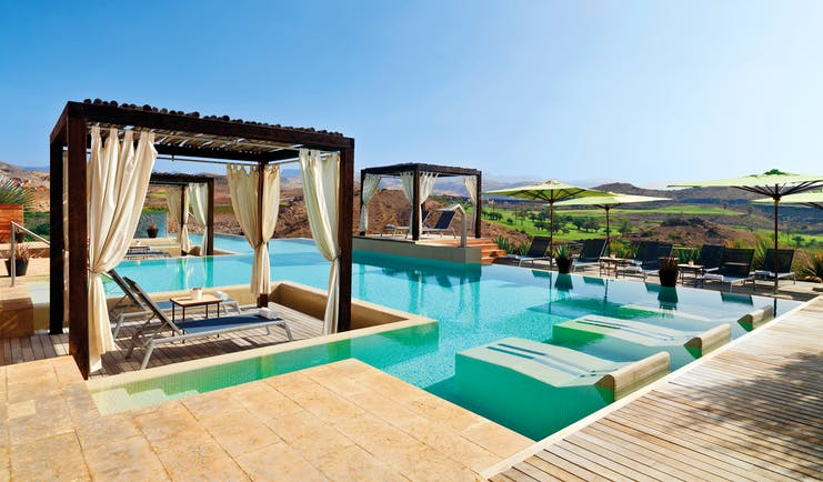 Outdoor pool with cabanas and sun beds around the outskirts of the pool