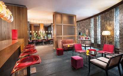 Restaurant with red colour scheme, stone walls and a wooden bar area