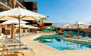 Swimming pool with sun loungers and umbrellas set up around the edge of the pool