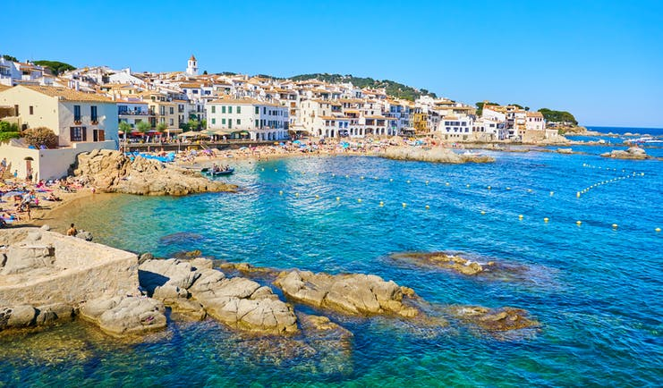 Blue sea lapping rounded rocks on coast with village behind at Palafrugell in Catalonia