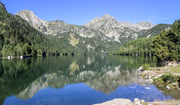 Lake with clear water surrounded by pine-clad hills and grey rocky mountains in Catalonia