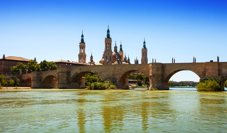 Stone bridge over wide river with the skyline dominated by the ornate spires of Zaragoza cathedral