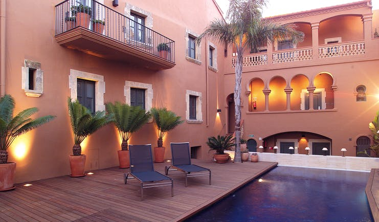 Gran Claustre Eastern Spain exterior pool sun loungers balcony potted plants