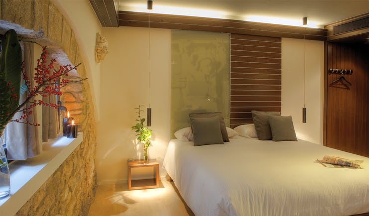Bedroom with stone walls, candles, large double bed and wardrobe