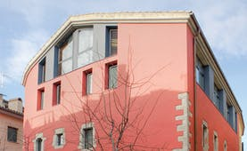 Exterior of hotel with pink and grey building with rectangular windows