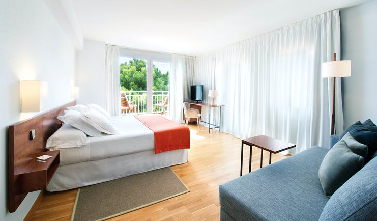 Bedroom with large double bed, doors opening onto balcony