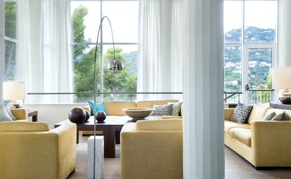 Lounge area with cream and yellow colour scheme, with sofas set out for seating