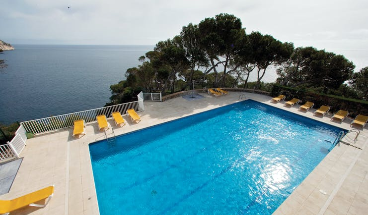 Outdoor pool with yellow sun loungers surrounding the pool and the sea in the background