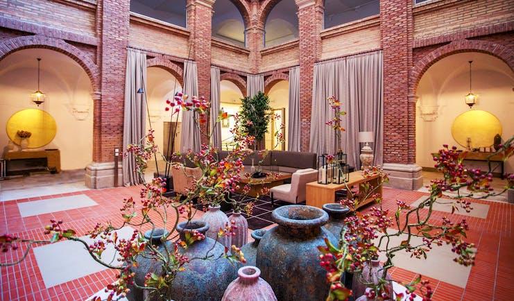 Parador de Lleida lobby, sofas, plants, exposed brick decor, red tiles