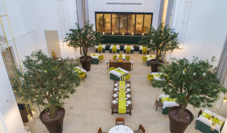 Parador de Lleida restaurant, dining tables, chairs, indoor trees, elegant decor