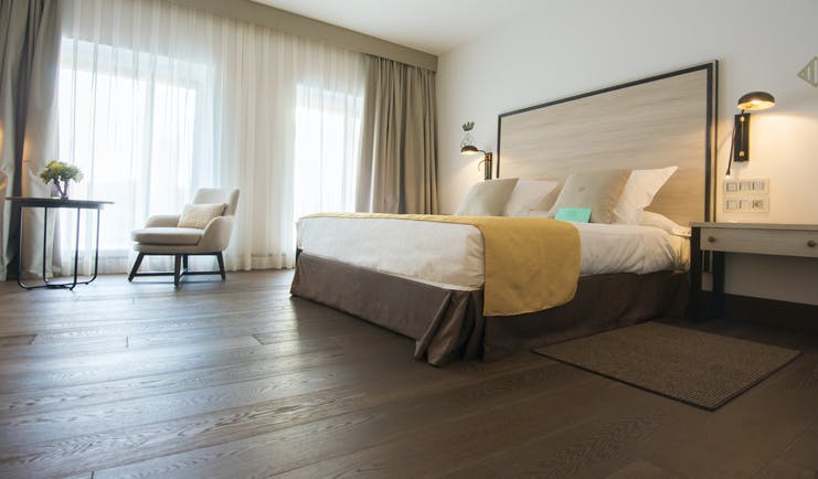 Parador de Lleida standard room, double bed, chair, large windows, pine floors and furniture