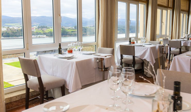 Parador de Ribadeo restaurant, tables, chairs, large windows with views over lake and mountains