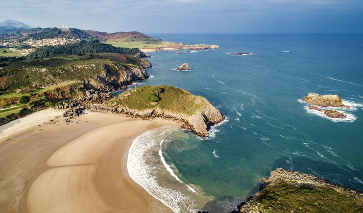 Sweep of golden sand beach with cliffs and headland in distance at Llanes in Asturias
