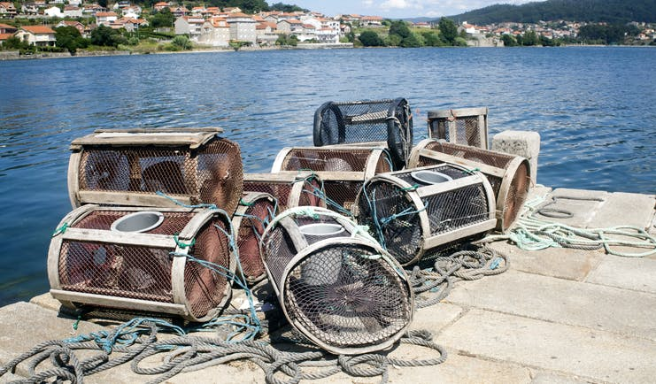 Lobster pots on quayside with blue sea behind in Pontevedra in the Rias Baixas in Galicia