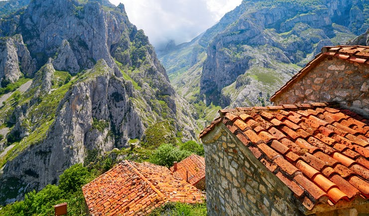 Rugged grey peaks with clouds and stone huts with red tiled roofs in foreground in the Picos de Europa