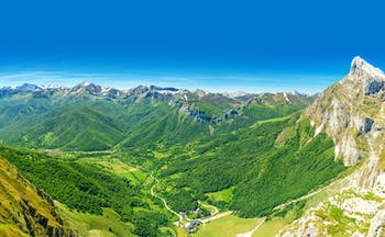 Wooded valley below mountains with snow on tops in the Picos de Europa in Cantabria