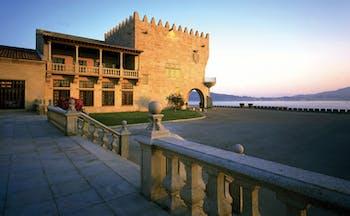 Parador de Baiona Green Spain exterior hotel building stone steps sea in background