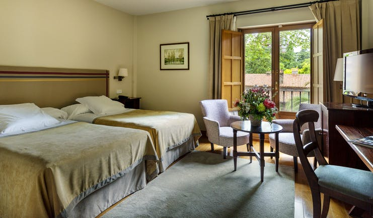 Parador de Gijon standard room, twin beds, table and chair, traditional decor