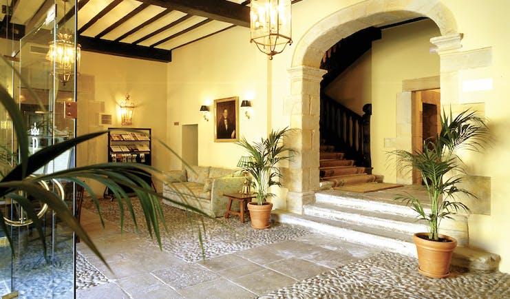 Parador de Santillana Gil Blas Green Spain lobby sofa plants stone floor rustic décor