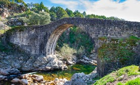 Old stone bridge over small river with rocks below and cliffs behind in the Sierra de Gredos Extremadura