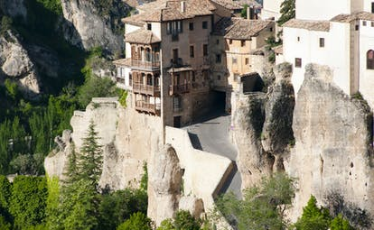 Houses with wooden balconies overhanging each other on the cliff sides of the gorge in Cuenca