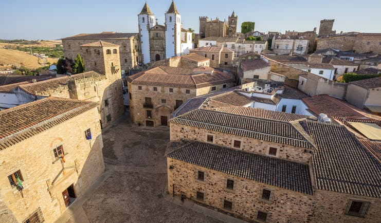 Stone buildings with tiled roofs and white and brown church with towers in Caceres