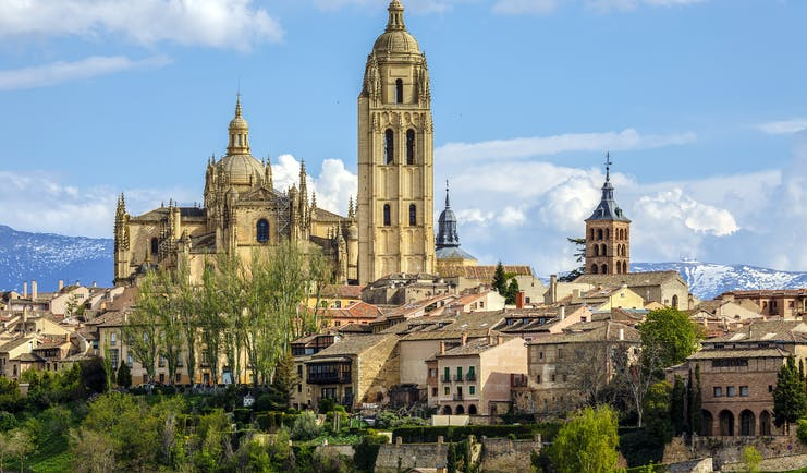 Tall spire and towers of the cathedral and city centre buildings from a distance at Segovia