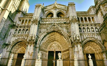 Entrance to Toledo cathedral with three doors of stone with intricate carvings
