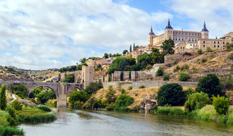 River in foreground with the square shape of the alcazar of Toledo on the hilltop above the city