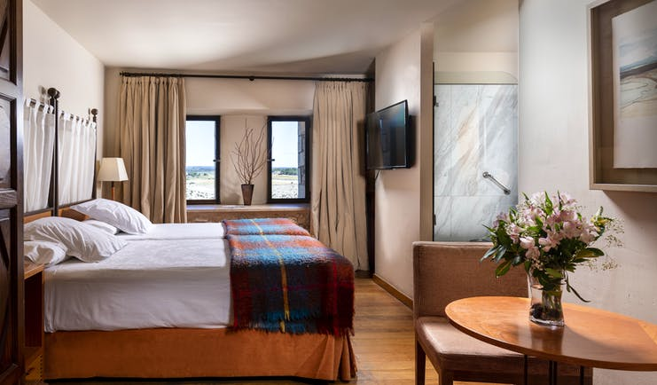 Parador de Alarcon twin bedroom with wooden floor and tweed blanket