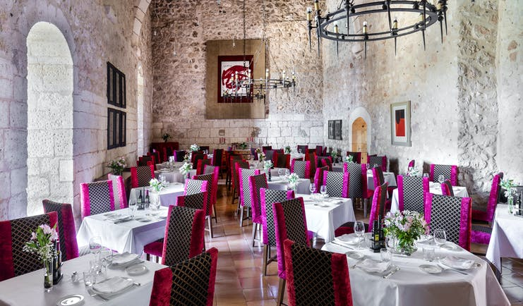 Parador de Alarcon dining hall with stone walls and pink chairs