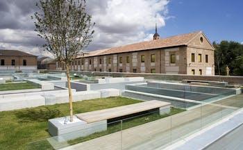 Parador de Alcala de Henares gardens, lawns, trees, hotel buildings, modern garden benches