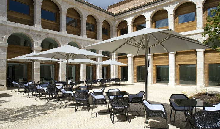 Parador de Alcala de Henares terrace, outdoor seating area, tables and chairs, hotel building