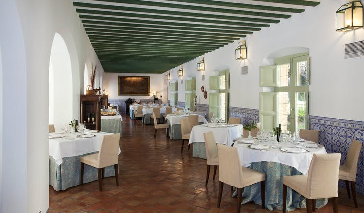 Parador de Almagro restaurant, dining tables, chairs, tiled floor, traditional architecture