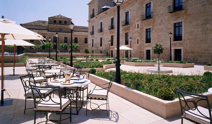 Parador de Lerma terrace, outdoor dinign area, patio, garden beds, hotel building