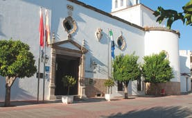 Exterior entrance to hotel showing white stone building with flags outside