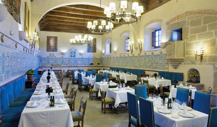 Restaurant with tables and blue chairs set out for dining and chandeliers hanging from the ceiling