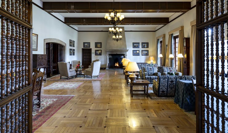 Parador de Tordesillas lounge, traditional decor and architecture, sofas, armchairs, candelabra, open fire