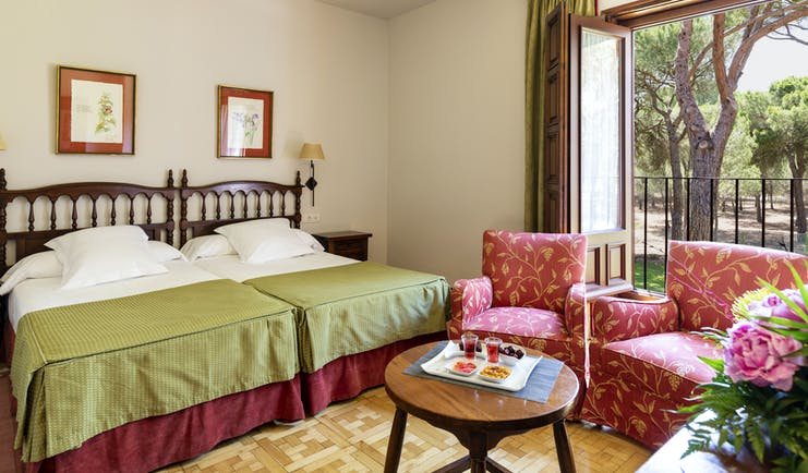 Parador de Tordesillas standard room, twin beds, traditional decor, armchoirs, garden view