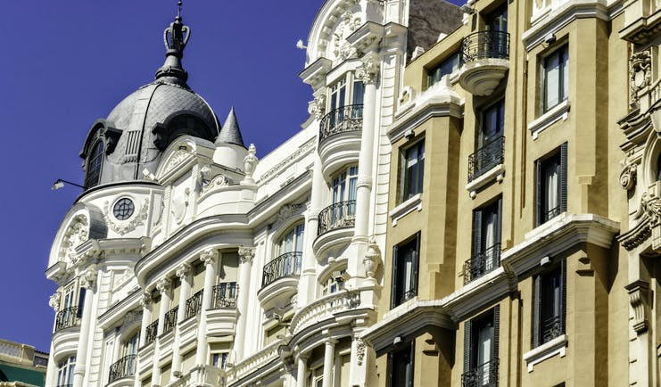 Tall 19th century houses white and yellow with balconies in La Gran Via in Madrid
