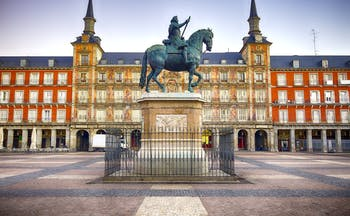 Equestrian statue in bronze with orange facade to buildings lining the arcaded square of the Plaza Mayor in Madrid