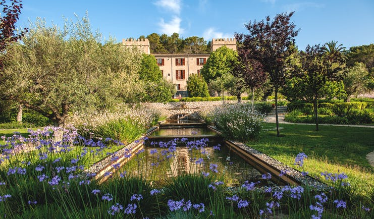 Castell Son Claret Mallorca front garden ponds lawns trees flowers hotel in background