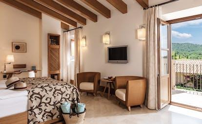 Castell Son Claret Mallorca terrace deluxe suite bed armchairs terrace modern décor