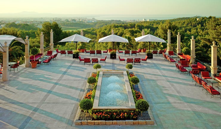 Main terrace with fountain, seating areas and umbrellas looking out over greenery