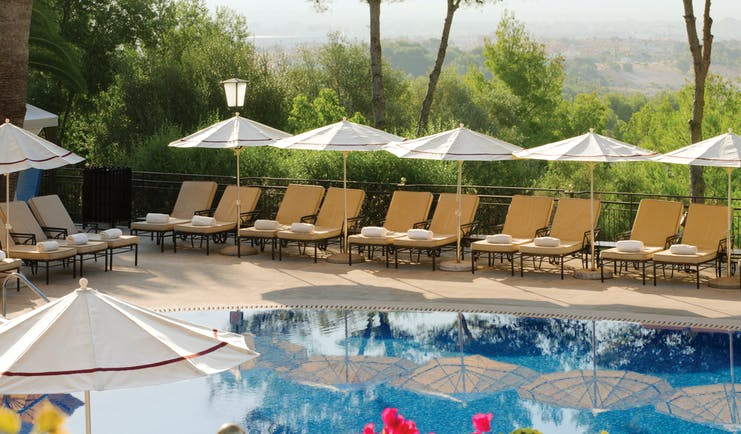 Outdoor pool with umbrellas and sun loungers set up around the pool and pink flowers shown nearby