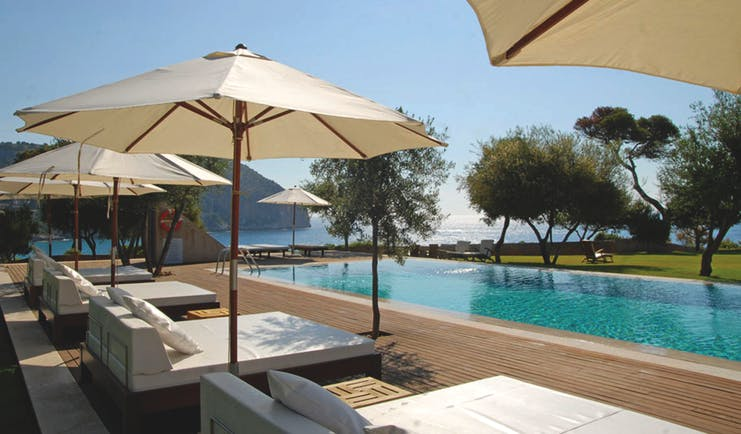 Can Simoneta Mallorca outdoor pool sun loungers umbrellas views of sea