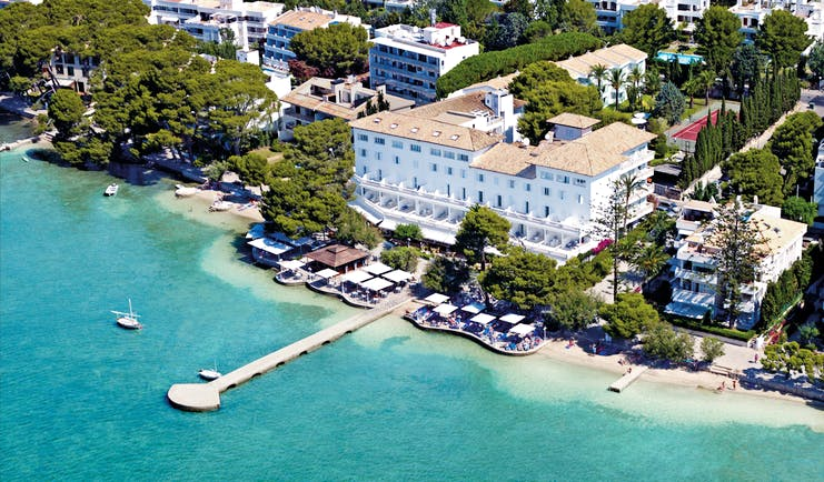 Aerial view of the hotel showing white building and pier over the sea