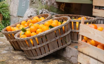 Baskets and crates of oranges with some greenery in Mallorca
