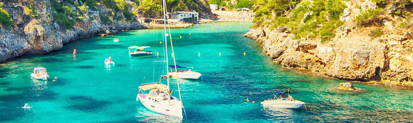 Turquoise waters in rocky cove with moored sailing boats