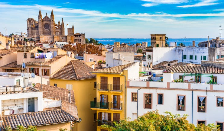 Narrow houses in shades of yellow, white and pink of the old town with rooftops and washing looking to the cathedral in Palma Mallorca